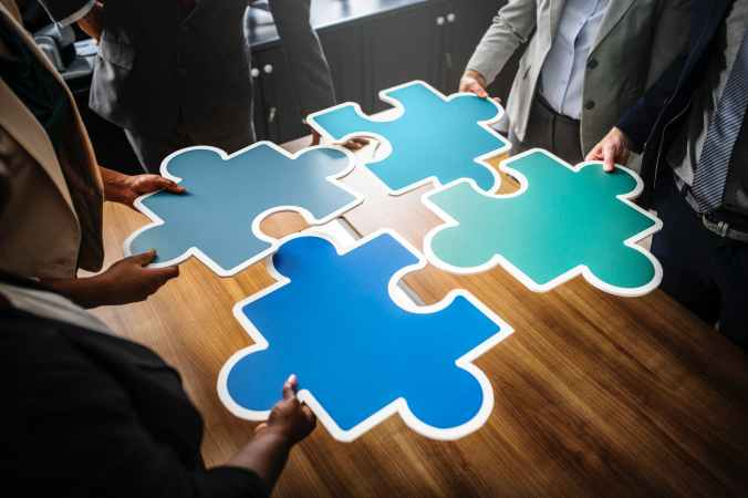 four people holding blue puzzles